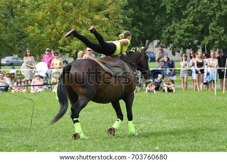 RIGA, LATVIA - AUGUST 19, 2017: Equestrian club member shows performance of vaulting on horseback within city day on August 19, 2017 in Riga, Latvia. The city day celebration is held annually.