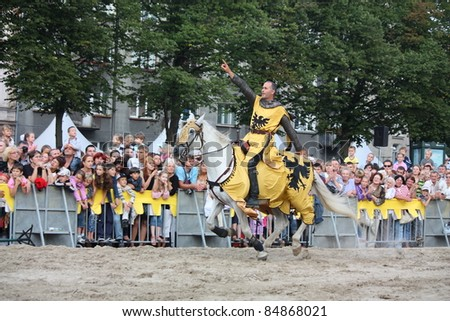 RIGA, LATVIA - AUGUST 21: Member of The Devils Horsemen stunt team riding horse and showing stunts during Riga Festival on August 21, 2011 in Riga, Latvia