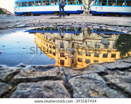 Riga Latvia capital city reflecting in a puddle on cobblestone street after the rain during golden hour before sunset with a man standing in background and a tram - stock photo