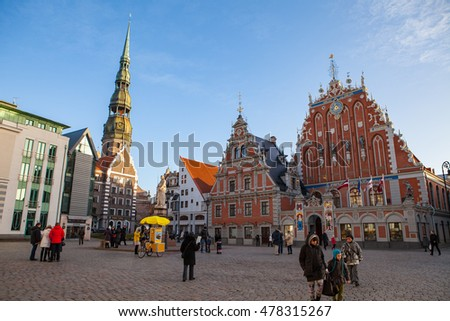 RIGA, LATVIA - 25 DEC 2015. People walking by town hall square at Chrismas time. St.Peter Church and House of the Blackheads.