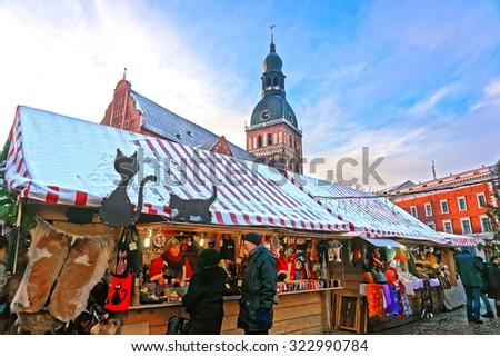 RIGA, LATVIA - DECEMBER 28, 2014: People buying traditional souvenirs at a European Christmas market in Old Riga, Latvia - stock photo