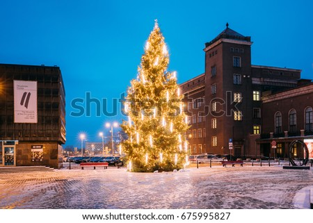 Riga, Latvia - December 14, 2016: Winter Night View Of Museum Of The Occupation Of Latvia, Xmas Christmas Tree And Riga Technical University RTU In Night Illuminations Lights. New Year Holiday Evening