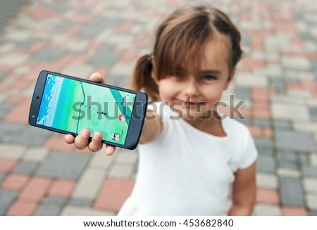 Riga, Latvia- July 17, 2016: Little girl playing a Pokemon Go game outdoors. Pokemon Go is a popular virtual reality game for mobile devices - stock photo