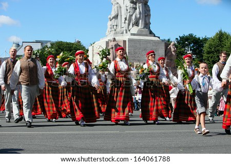RIGA, LATVIA - JULY 06: People in national costumes at the Latvian National Song and Dance Festival on July 06, 2013. Holiday was hold from 30th June 2013 to 7th July 2013.  - stock photo