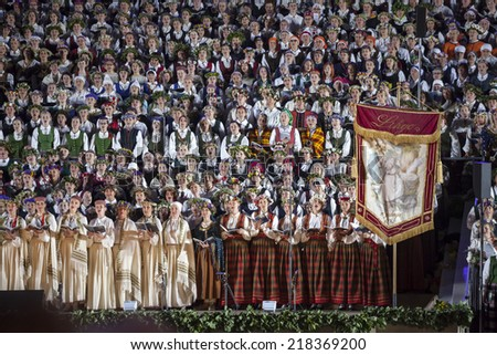 """RIGA, LATVIA - July 7, 2013: The Latvian National Song and Dance Festival Grand Finale concert """"Ligo!"""". Singers with historical festival flag. - stock photo"""