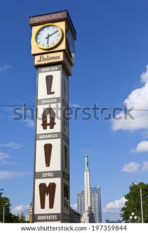 RIGA, LATVIA - JUNE 3RD 2014: The Laima Clock in Riga on 3rd June 2014.  The Freedom Monument is seen in the background. - stock photo