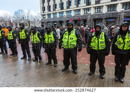 Riga, Latvia - March 16, 2014: Latvian Legion Day. Policemen units for conflict prevention before Legionnaires walk at the Freedom Monument
