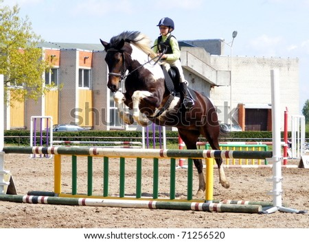RIGA, LATVIA - MAY 17: An unidentified girl show jumps on classification competition in show jumping with pony in Riga, Latvia on may 17, 2008. - stock photo