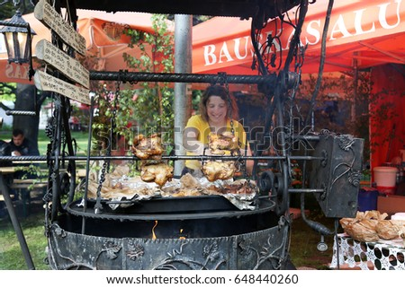 RIGA, LATVIA - MAY 25, 2017: Participant of the public open festival LATVIA BEER FEST cooks traditional meat snacks shown on May 25, 2017 in Riga, Latvia. The festival is held annually