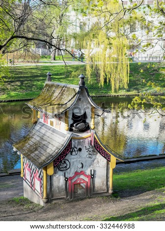 Riga, Latvia - May 3: Small decorative chinese house in Bastejkalns park in Riga, Latvia on May 3 2015. The park contains memorials to those who died there in Latvia's struggle for freedom in 1991. - stock photo