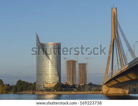 RIGA, LATVIA - SEPTEMBER 15, 2013: View on modern building of Swedbank and new tower buildings under construction on the left bank of Daugava river in Riga - capital of Latvia, Europe