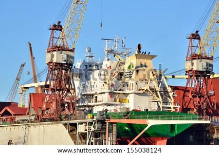 Riga shipyard with a cargo ship in the dock - stock photo