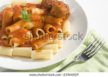 Rigatoni pasta and Meatballs dinner. Topped with basil garnish.