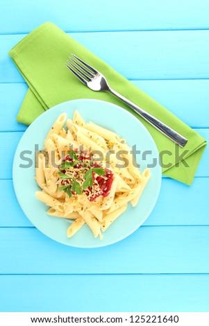 Rigatoni pasta dish with tomato sauce on blue wooden table - stock photo