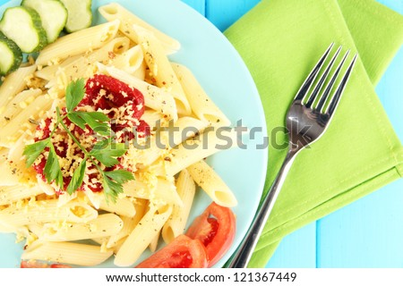 Rigatoni pasta dish with tomato sauce on blue wooden table close up