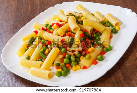 rigatoni pasta with mixed vegetables on white plate