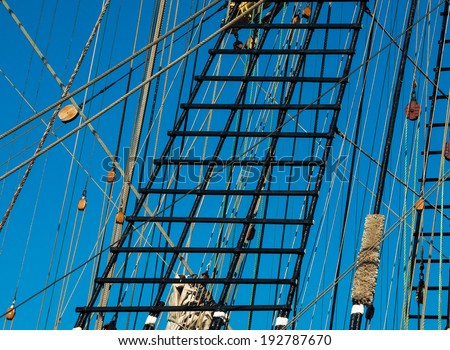 Rigging ropes and pulley at the old ship. Tackles of the ancient sailing vessel. Marine background with wooden rigging and rope ladder. Wooden block, ladder upstairs on the mast. Tackle on the ship. - stock photo