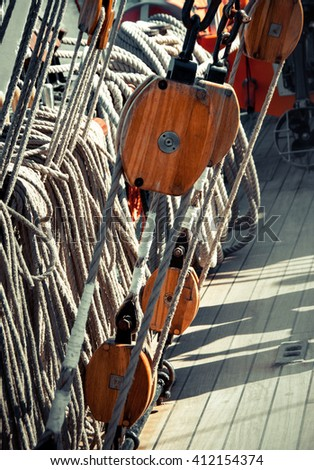 Rigging ropes and pulley at the old ship. Tackles of the ancient sailing vessel. Marine equipment - wooden rigging and ship ropes. Wooden block and tackle of the mast on the ship. - stock photo