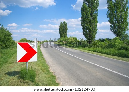 Right arrow direction sign by the curvy road at sunny day - stock photo