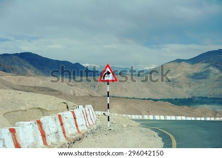 Right Curve Road Sign with Background of Mountain, Cloud and Blue Sky in Leh - Ladakh, North of India - stock photo