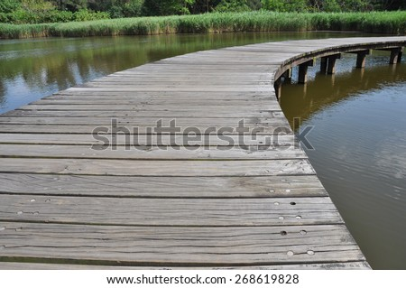 Right curve wooden bridge path in lake at wetland park - stock photo