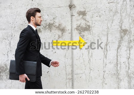 Right direction. Handsome young man in formalwear holding briefcase while walking in front of the concrete wall  - stock photo