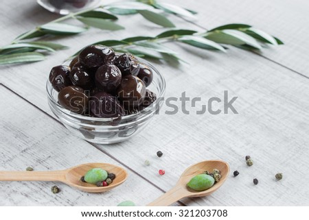 Right free space, on the left in the middle frame bowl with olives framed by branches of the olive tree, wooden spoons with olives on a white wooden background. Black sundried olives and empty space. - stock photo