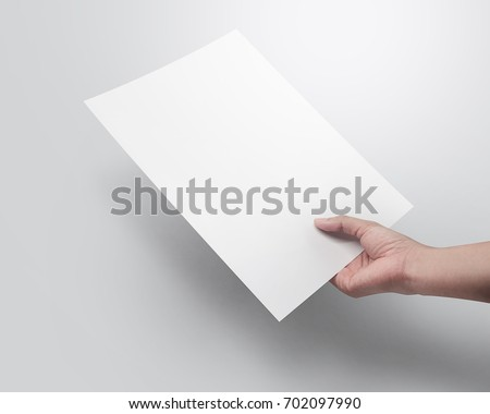 Right hand holding blank paper sheet A4 size or letter paper on grey background.