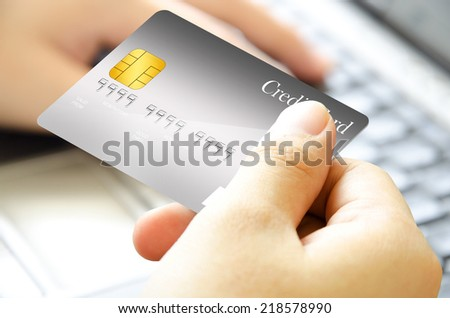 Right hand holding the credit card and left hand touch on the computer keyboard for inputting the card code. - stock photo