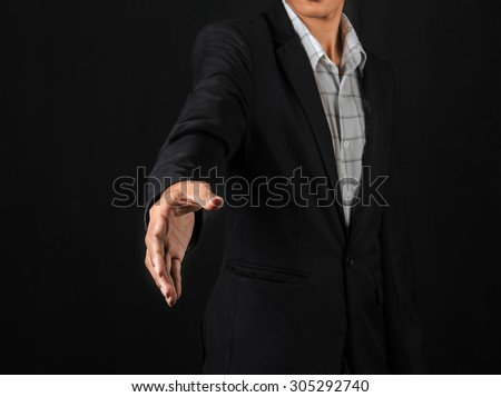 right hand of a man, wearing black business suit, ready for a handshake, symbol of agreement or partnership, on black background.select focus - stock photo
