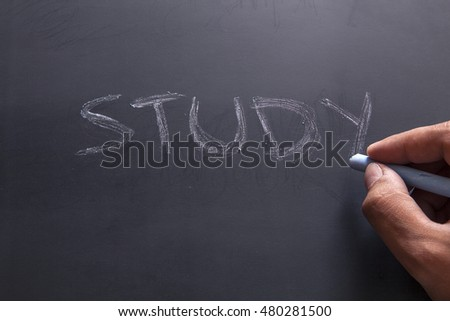 Right hand writing word study on blackboard using chalk, selected focus on the board