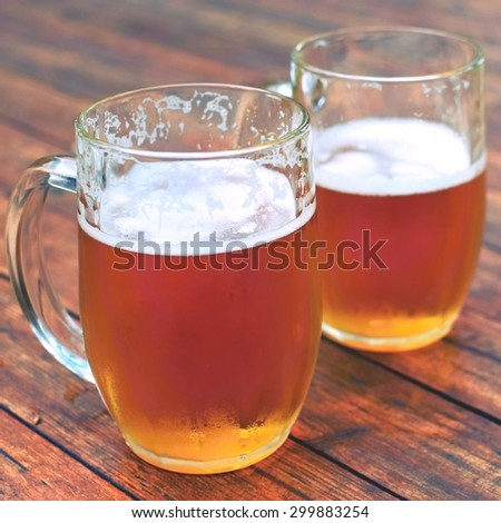 Right honest Czech draft beer - a lager in a glass on a wooden background. Glass of beer. - stock photo