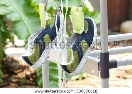 right shoe tongue (selected focus) of green and deep blue canvas shoes and shoestring drying hangs on by clothespin and another one at home - stock photo