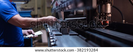 right side close-up of a worker holding a metal plate against a manufacturing machinery, in the right hand, and several other metal plates in his left hand - stock photo