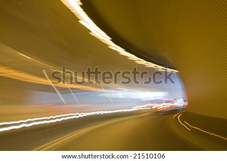 Right turn in tunnel with light tracks and light in the end of tunnel. Motion blur. Background texture.