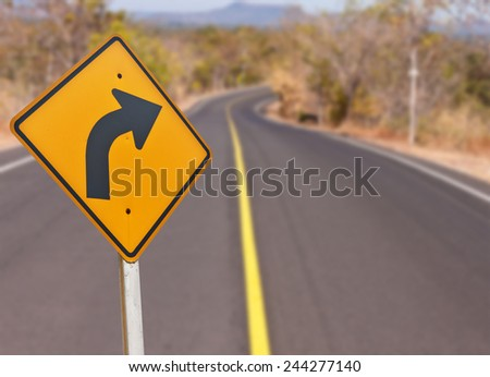 Right Turn Sign: A sign warns of a sharp right turn on a country road in northeast of Thailand. - stock photo