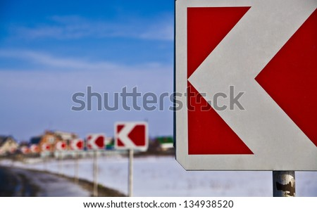 right turn sign   Frozen and snowed guide road sign of turn and houses  in a blue foggy background - stock photo