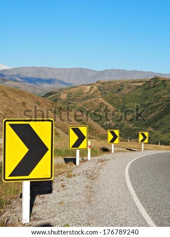 Right Turn Sign: Road signs warn of a sharp turn on a narrow road in New Zealand - stock photo