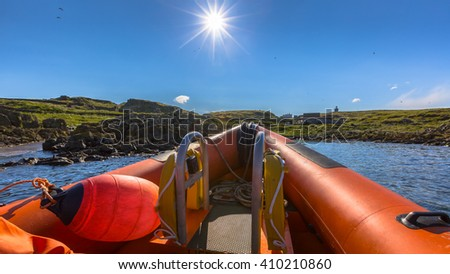 Rigid inflatable boat out on sea near an island on a sunny day - stock photo