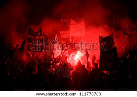 RIJEKA, CROATIA - SEPTEMBER 01: soccer match between HNK Rijeka (white) and HNK Hajduk (red-blue) ; soccer fans celebrating at the stadium on September 01, 2012 in Rijeka, Croatia - stock photo