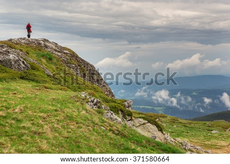 Rila mountains. A woman on the top of a rock enjoys the spring view of Rila mountains.