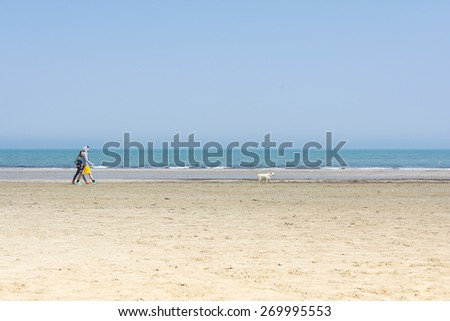 RIMINI,ITALY-APRIL 12,2015:A lonely couple stroll with the dog on the Rimini beach near the sea during a sunny day.