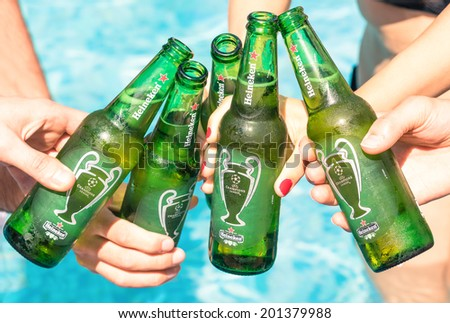 RIMINI, ITALY - JUNE 28, 2014: Heineken bottles toasting against blue water. Heineken Lager Beer is produced by the Dutch brewing company Heineken International and exported all over the world. - stock photo
