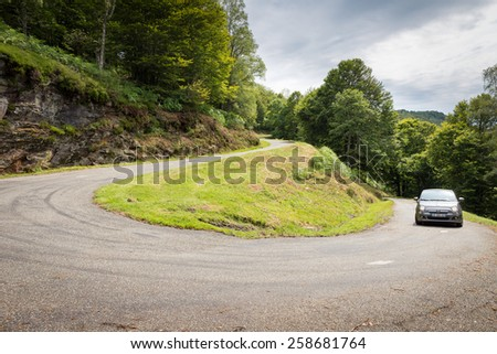 RIMONT, FRANCE - JULY 24, 2014: Fiat 500 (Type 312) driving up a winding road to Col de Peguere. The Fiat 500 hatchback is a city car built by Italian automaker Fiat since 2007. - stock photo