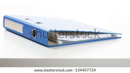 Ring binder in blue color, lying on a desk. Studio shot, isolated on white. - stock photo