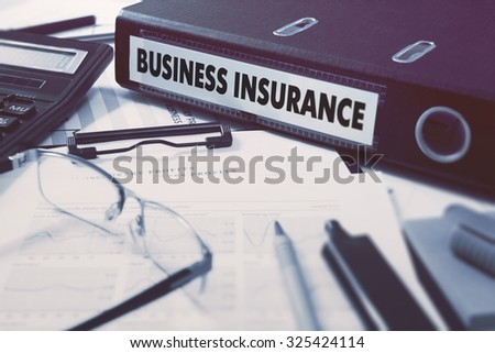 Ring Binder with inscription Business Insurance on Background of Working Table with Office Supplies, Glasses, Reports. Toned Illustration. Business Concept on Blurred Background. - stock photo