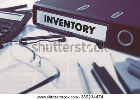 Ring Binder with inscription Inventory on Background of Working Table with Office Supplies, Glasses, Reports. Toned Illustration. Business Concept on Blurred Background. - stock photo