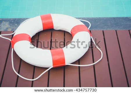Ring buoy on swimming pool.Red lifebuoy on swimming pool. - stock photo