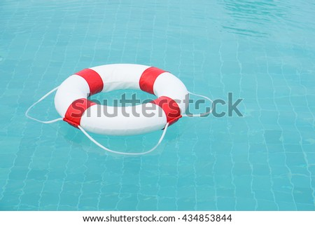 Ring buoy on swimming pool.Ring buoy on the water.Red lifebuoy on swimming pool.Life buoy. - stock photo