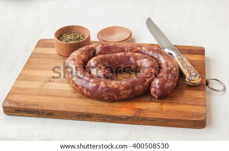 Ring homemade raw liver pork sausage on a cutting board - stock photo